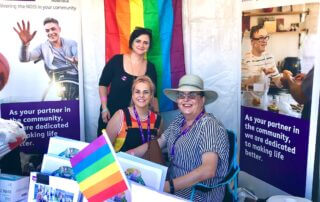 Smiling NDIS team at the Carers Queensland Pride stall