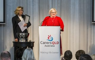 "Kylie Minns making a speech at the podium after winning the ""Why do I care?"" writing competition at the 2018 Gala Lunch"