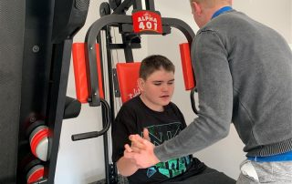 Connor on exercise equipment with his trainer