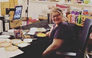 Deb sitting in her art studio smiling
