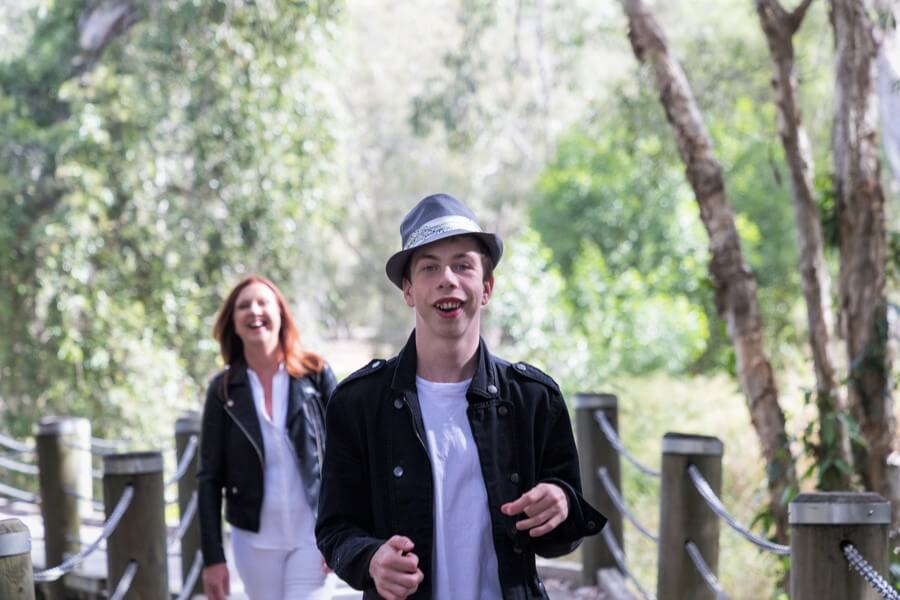 Dylan walking in a park with a lady in the background