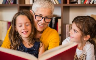 Woman with glasses and short blonde hair reading to young girl and boy