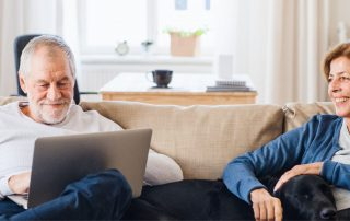 Man and woman sitting on couch with dog in between them. Man on laptop, woman smiling at man.
