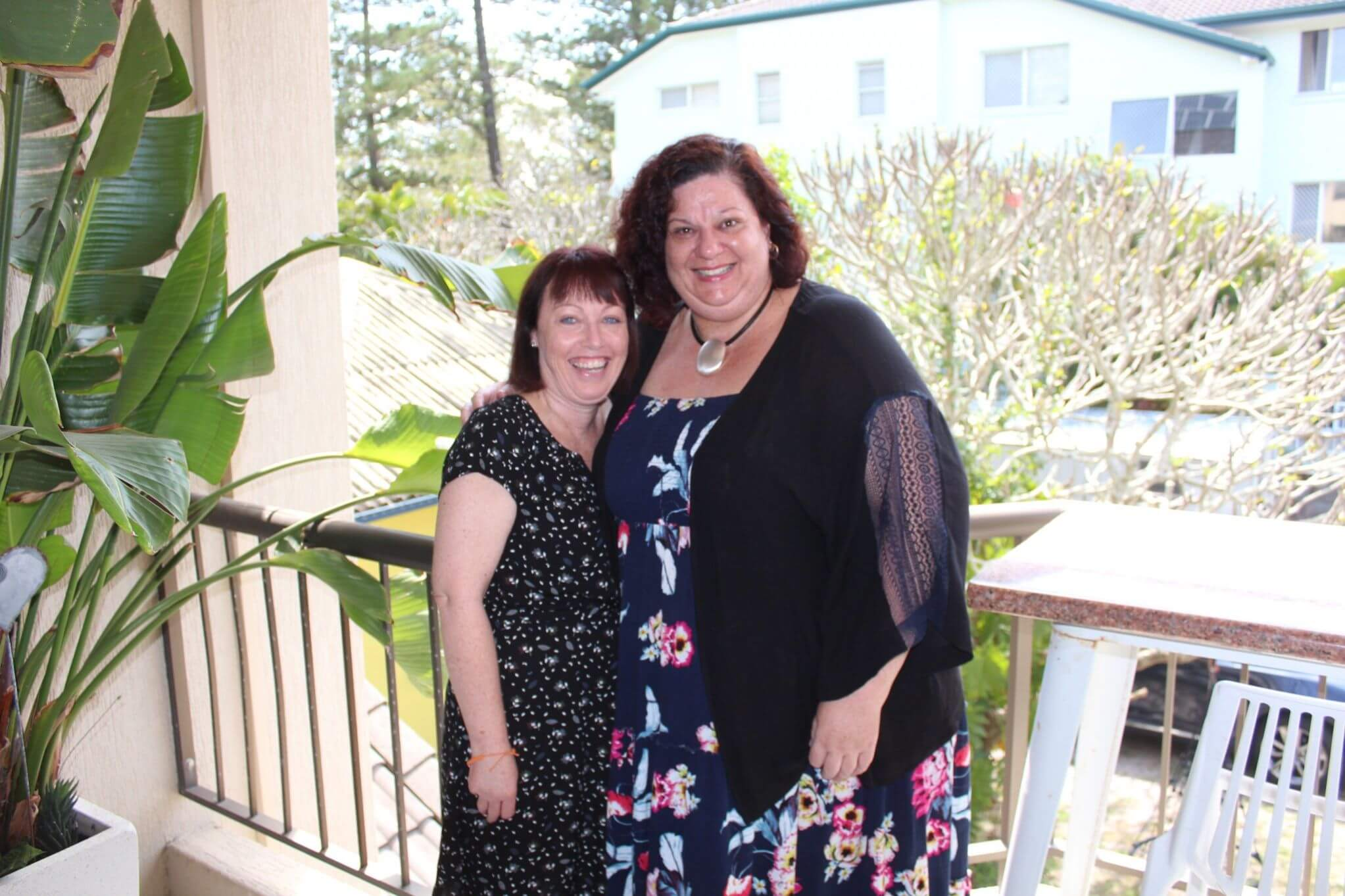 Jody and Sylvia - two women standing on a balcony smiling