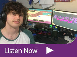 Game developer Bradley Hennessey, who has ASD, sitting in front of his computer. On the screen we see the loading screen for his game An Aspie Life.