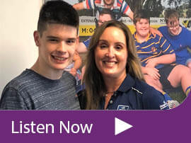 """Max Elliot and his mum Megan stand in front of a poster for the Modified Rugby Program. Text at the bottom says """"listen now""""."""