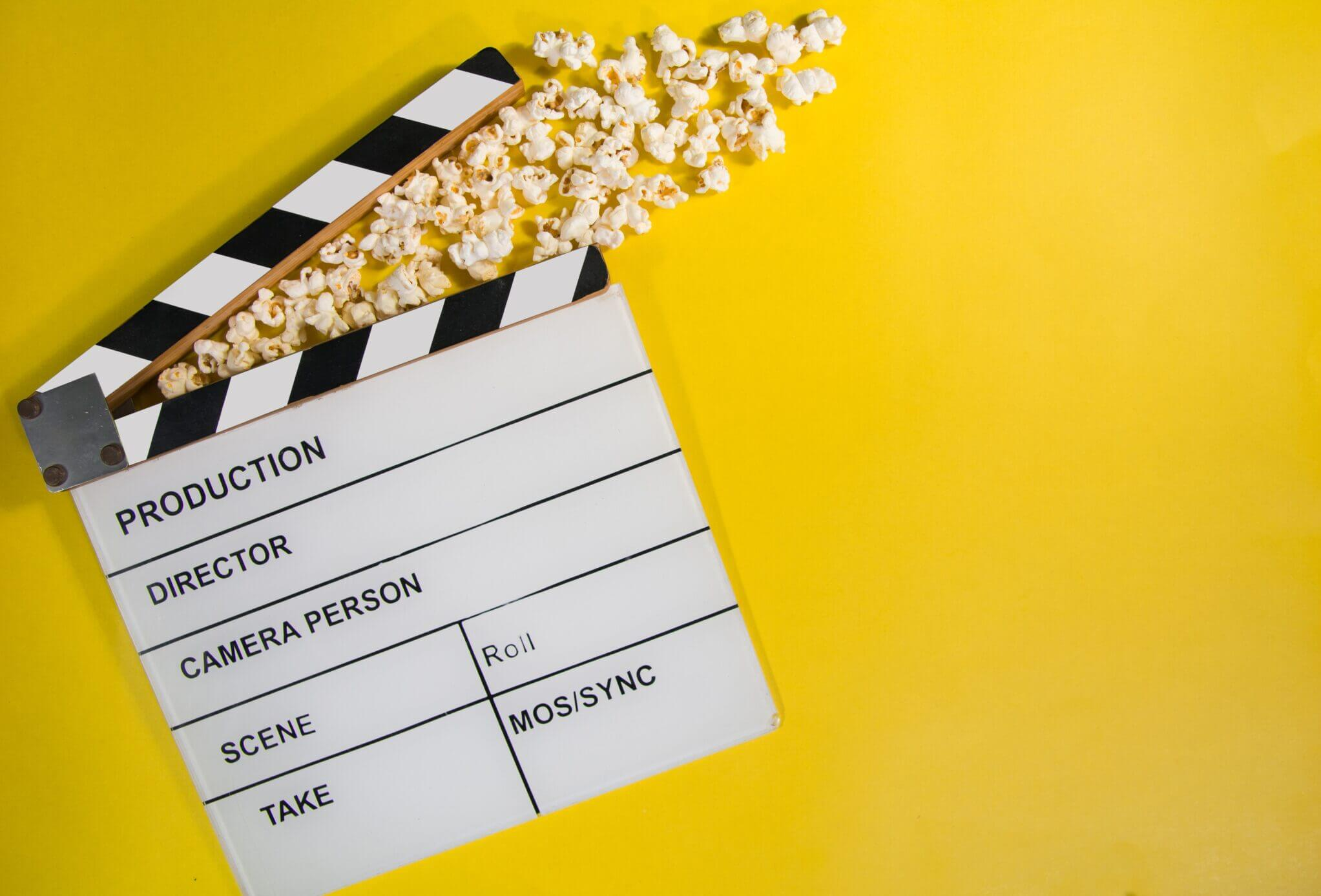 Popcorn and clapperboard on a yellow background