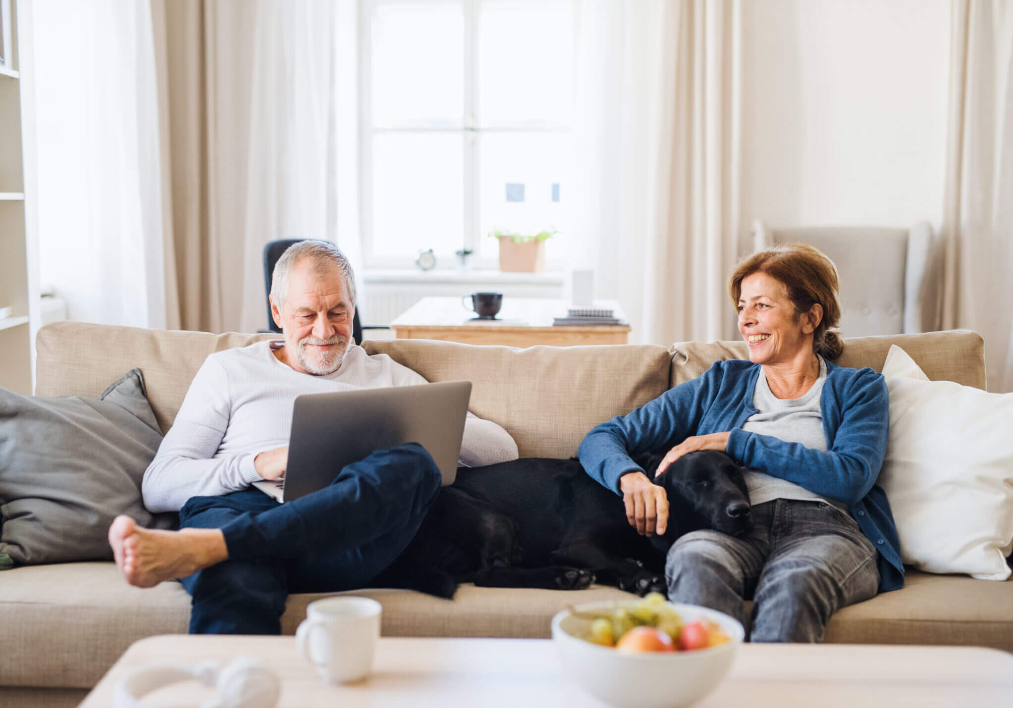 Man and woman sitting on couch with their dog between them. Man on computer, woman smiling at man.