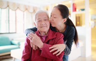 Younger woman hugging elderley woman from behind