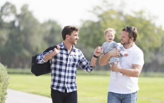 Two men walking in a park together, one holding a baby and the other engaging with the baby