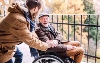 Young man communicating with an older gentleman in a wheelchair, smiling